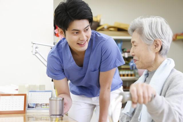 高齢者の女性と労う作業療法士